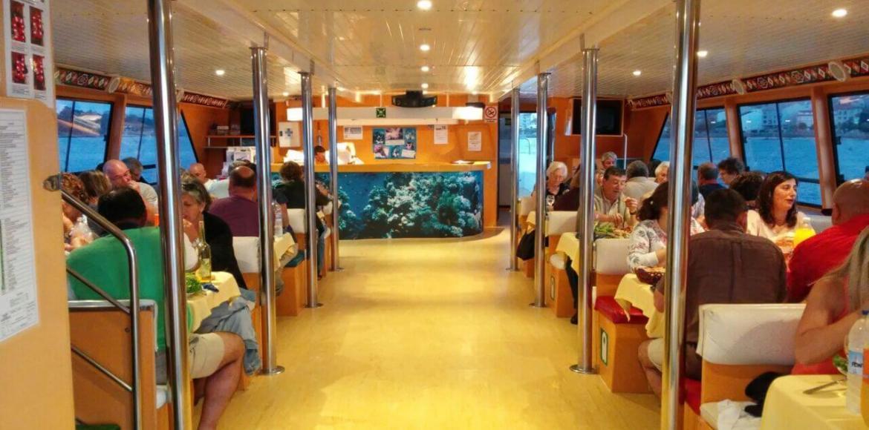 Vista Ampliada del Pasillo central del Barco Restaurante Fly Delfín con gente comiendo a bordo